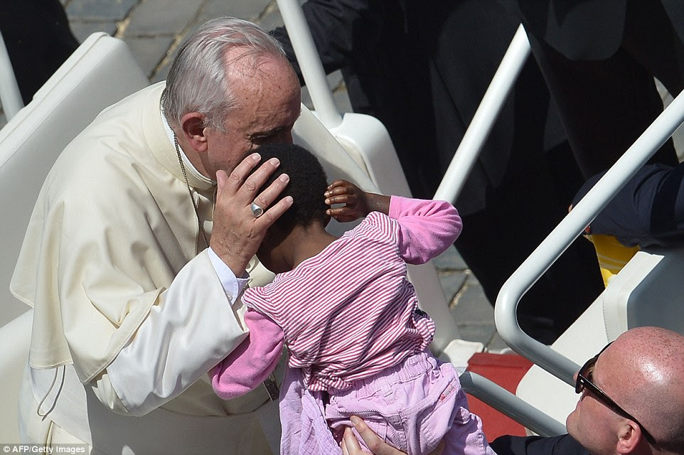 The Pope blesses a young child at the end of the Holy mass, tenderly touching her head as she was held up to him by members of the crowd