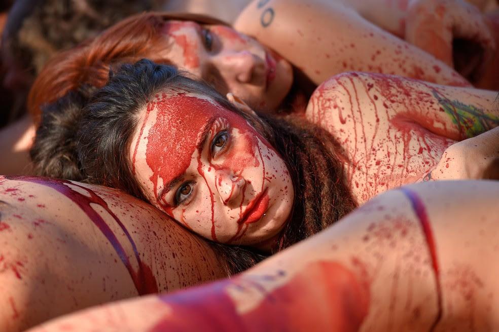 Manifestantes nus do grupo AnimaNaturalis, cobertos com sangue falso, protestam contra o uso de peles de animais em Barcelona (Foto: Lluis Gene/AFP)