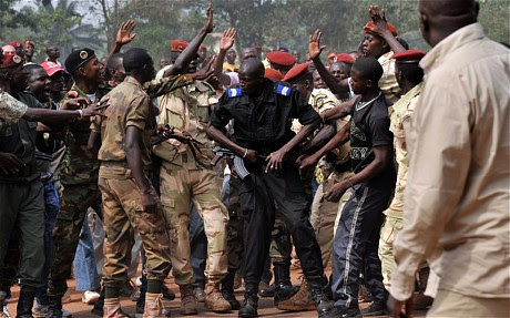 Central African Republic soldiers surround a policeman who sought to intervention to prevent the murder of a man accused of being a Seleka rebel. The incident occurred on Feb. 5, 2014. by Pan-African News Wire File Photos