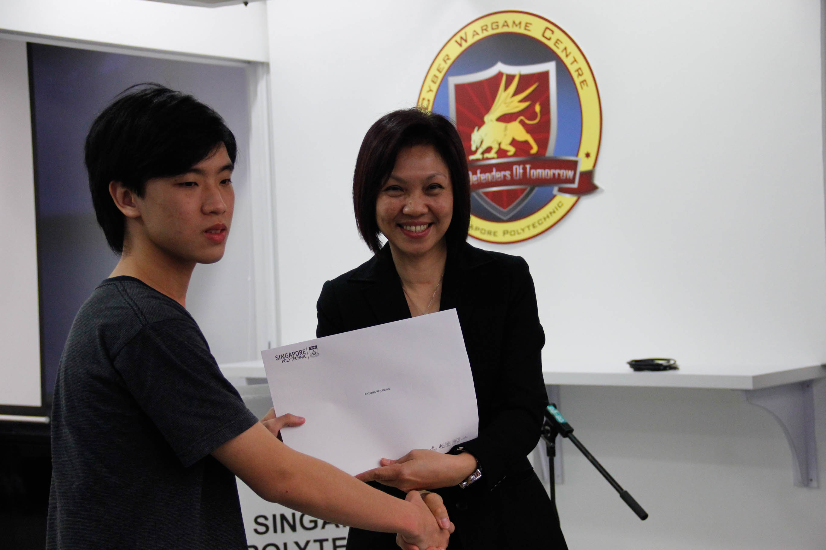 DMIT Director Ms Georgina Phua presenting Certificate of Participation in DISM CTF S1 to year 1 student Cheong Ren Hann
