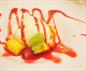 バニラジェラートにベリーのソースとマンゴー、苺を添えたデザート。