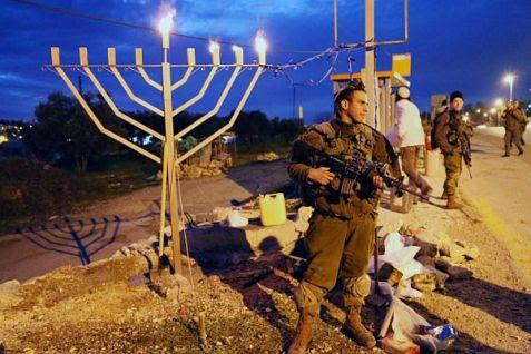 Hanukkah menorah lighting at 2014 terror attack site in Gush etzion.