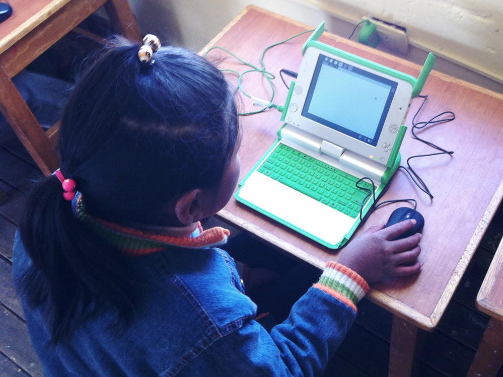 A young Peruvian student in the southern village of Lacachi village in southern Peru uses a laptop computer provided through a nationwide program. However, benefits have been limited so far. In some cases, proper software is lacking, Internet access is not available and some teachers have a limited understanding of how to use the computers.