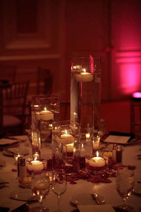 Different height vases with floating candles and rose