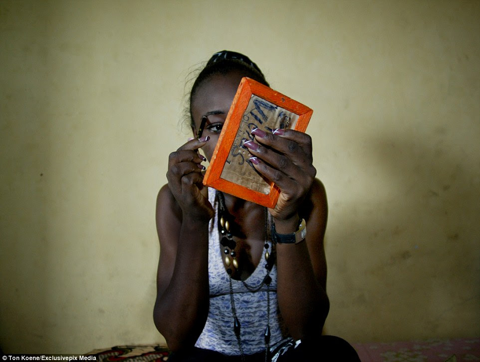 A woman adjusts her makeup in the Badia slum in Lagos, Nigeria, where hundreds of women are working in the sex trade