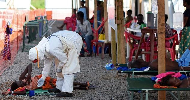 A nurse wearing personal protective equipment checks on a patient at the Kenema Ebola treatment center on November 15, 2014