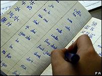 Un estudiante realiza anotaciones en su cuaderno en una clase de mandarín