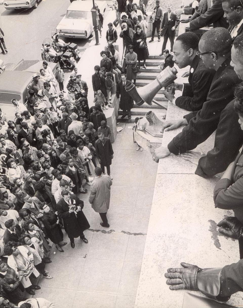 "April 22, 1965: The Rev. Martin Luther King Jr. used a bullhorn to address the crowd at the Patrick T. Campbell Middle School in Roxbury. On segregation he told the crowd, ""This is not a battle of white people against black people. It is a struggle between the forces of justice and injustice."""