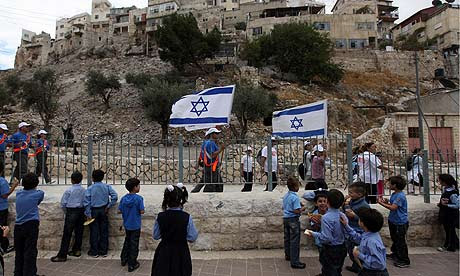 Palestinian children in a school courtyard as Israelis participating in a Sukkot celebration march