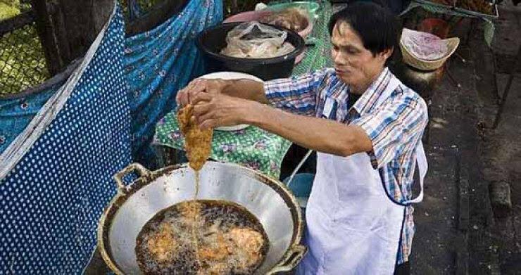 Tailandês coloca suas mãos no óleo fervendo sem queimar-se