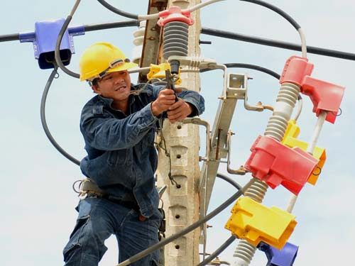 Công nhân Tập đoàn Điện lực Việt Nam cải tạo lưới điện trên đường Huỳnh Tấn Phát, huyện Nhà Bè, TP HCM