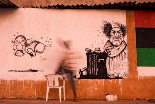 """A street artist paints a caricature of Libyan dictator Muammar Qaddafi and his spokesman Abdel-Majid al-Dursi, left, in the rebel-held town of Benghazi, Libya, on July 21, 2011.""  (via The Atlantic.)"