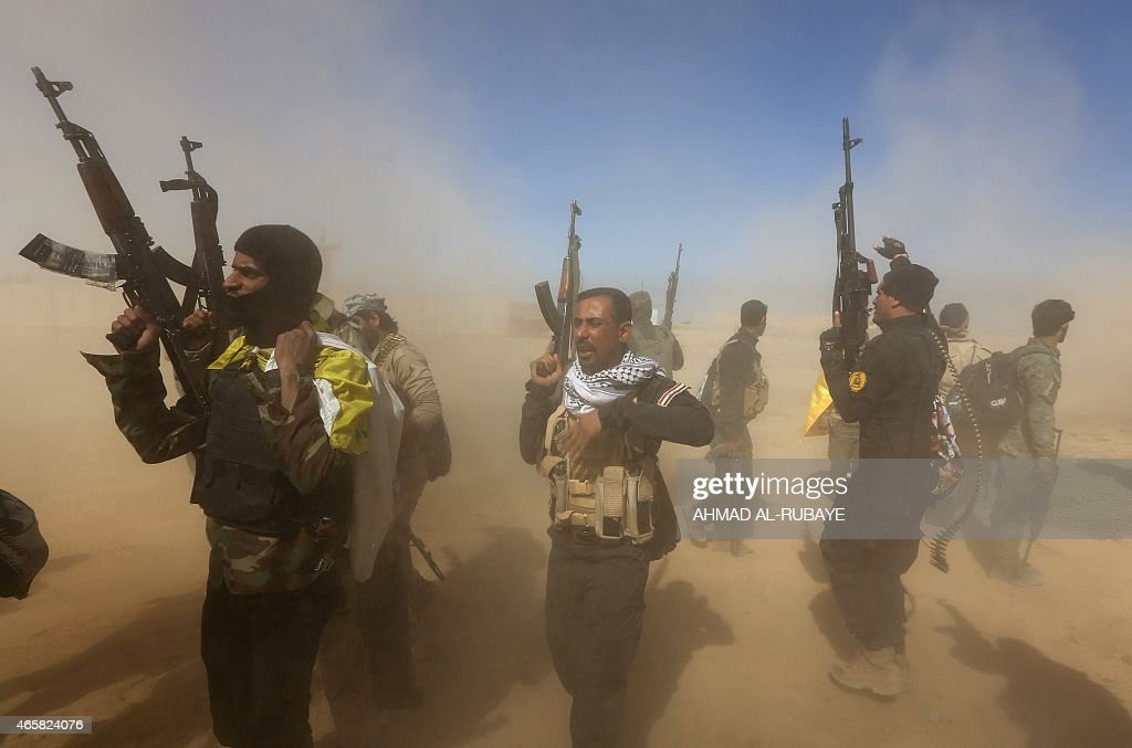 Iraqi fighters of the government-controlled Popular Mobilisation units gather on the western entrance of the Iraqi city of Tikrit during a military operation to take control of the city, 160 kms north of Baghdad, from jihadists from the Islamic state (IS) group, on March 11, 2015. The city, which is the home town of former president Saddam Hussein, is the toughest target for the government troops and allied militias that started winning back lost ground last year.