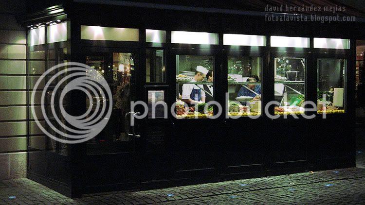 Vista a través de la cristalera del interior de un restaurante en Ginebra (Suiza) con los camareros y cocineros trabajando