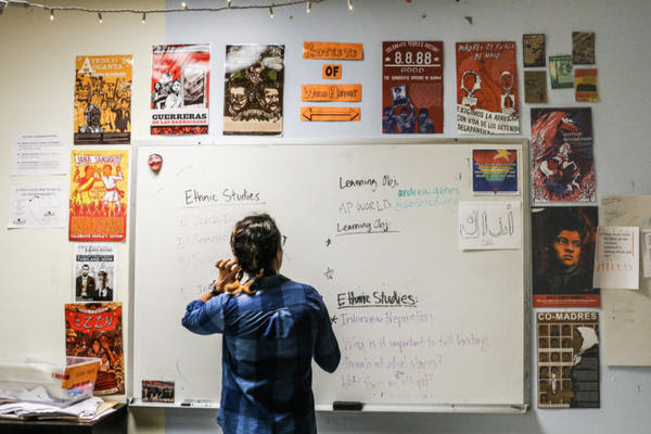 Andrea Gaines in front of her classroom whiteboard.