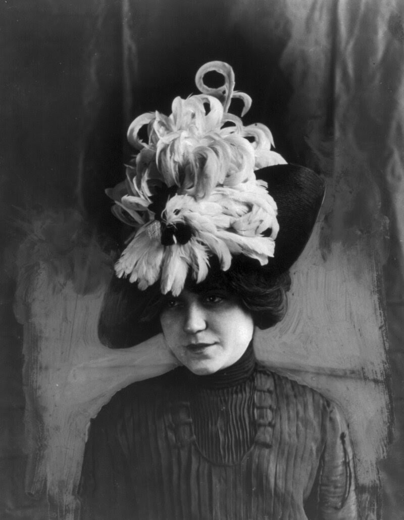 """Woman wearing a """"Chanticleer"""" hat made of bird feathers, circa 1912."""