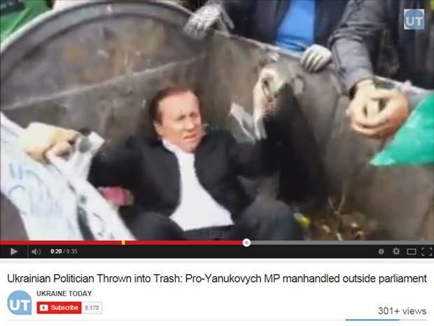Vídeo mostra momento em que manifestantes jogam deputado em lata de lixo perto do Parlamento ucraniano, em Kiev, nesta terça-feira (16) (Foto: Reprodução/Youtube/Ukraine Today)