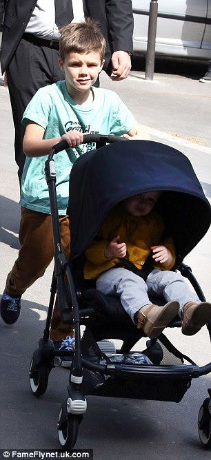 Responsible: The youngster took charge of the pushchair and even lowered Harper's sun visor when it got too bright