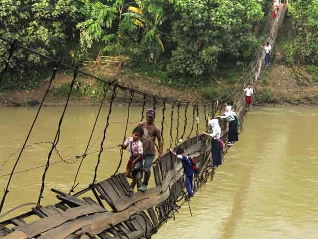 Crianças arriscam-se em ponte danificada sobre o Rio Ciberang, em Lebak, na província indonésia de Banten, para ir à escola nesta quinta-feira (19). A ponte foi atingida por uma tempestade que atingiu a região na semana passada (Foto: AP)