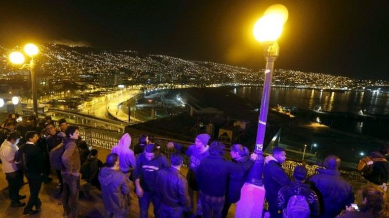 People stand and watch the ocean on Cerro Baron hill in Valparaiso. Photo: 16 September 2015