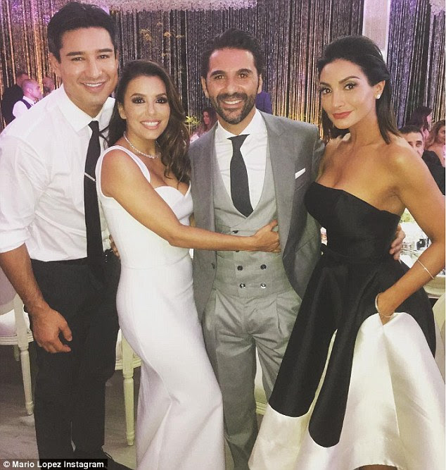 Blushing bride: Eva looked gorgeous in her  dress as she posed with her new husband and Mario Lopez