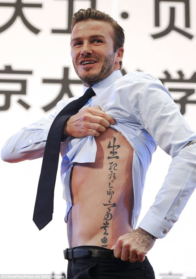 Flashing some flesh: David Beckham lifted up his shirt to reveal a tattoo while speaking to students at Peking university on Sunday