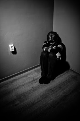 sad woman sitting alone in a empty room - black and white