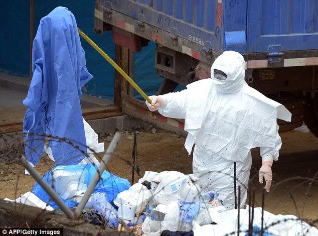 Um trabalhador em um terno EPI usa uma vara para mover lixo dentro da zona de alto risco em quarentena do hospital John Fitzgerald Kennedy, na Libéria. Funcionários da Libéria, confirmou hoje que um quartel de polícia no centro de Monróvia foi encerrado após a esposa de um dos policiais morreu de Ebola