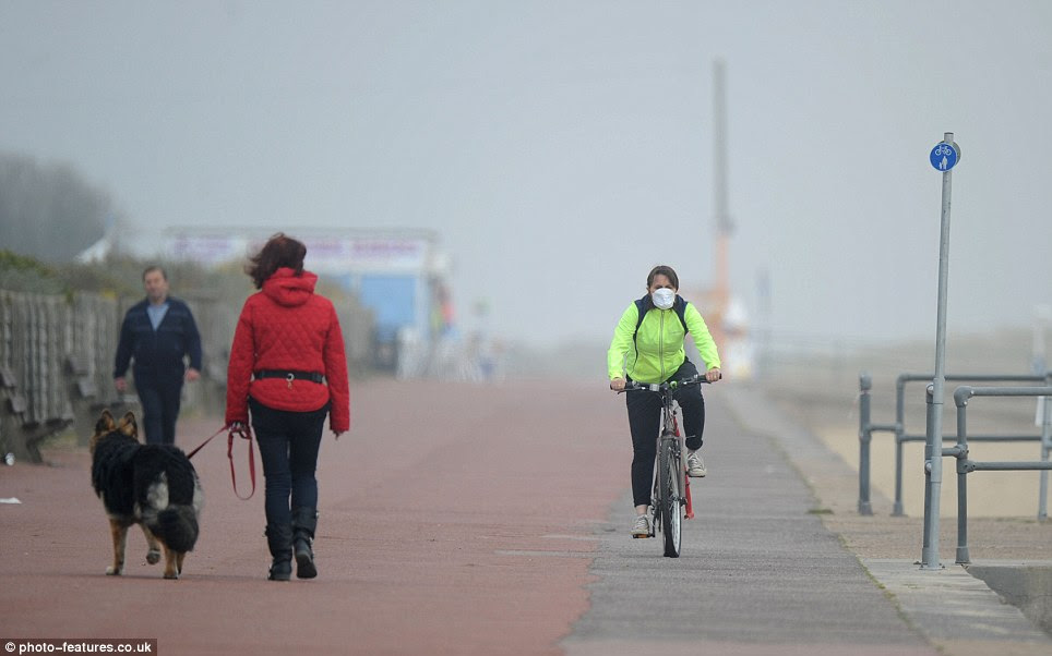 Protection: A cyclist uses a pollution mask in Great Yarmouth, Norfolk, as a potentially-lethal cloud of Saharan sand, toxic air and local pollution sits over Britain