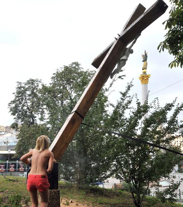 Integrante do grupo Femen corta cruz ortodoxa (Foto: AFP)
