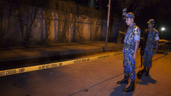 Police officers stand guard at the site where an Italian charity worker has died after being shot by attackers in Dhaka