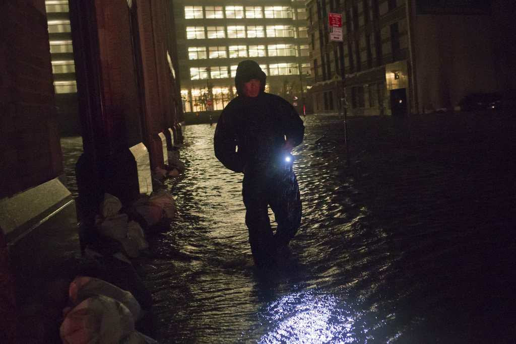A security guard walks through a flooded street in the financial district of Manhattan, New York. NYSE Euronext said it is preparing to implement a new contingency plan to help resume stalled U.S. equity trading, and added that its famed trading floor is not yet damaged by Hurricane Sandy.