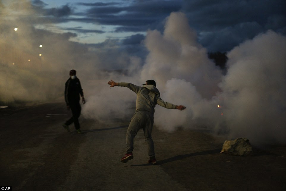 A demonstrator throws stones at French riot police officers during clashes in a makeshift migrant camp near Calais, France