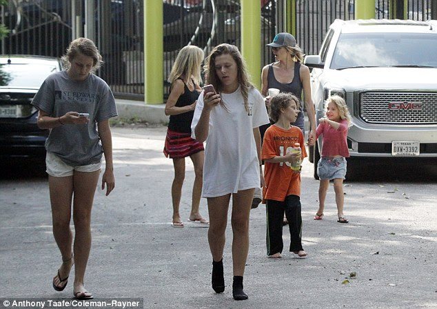 All five of Armstrong's children came out on the water on Sunday. Hansen pictured in a hat, holding the hand of their daughter Olivia, 4, behind their son Max, 5, while Armstrong's oldest daughters with ex-wife Kristen Richards (13-year-old twins Grace and Isabelle) stare intently at their phones in the lead