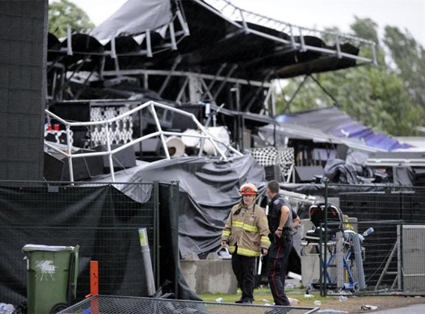 Emergency workers walk in front of the twisted debris that was an Ottawa Bluesfest stage. The stage collapsed Sunday, July 17, 2011.