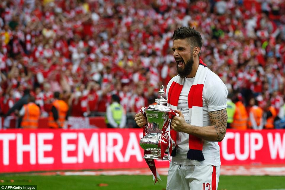 French striker Olivier Giroud roars with delight as he holds the FA Cup while wearing a personalised T-shirt