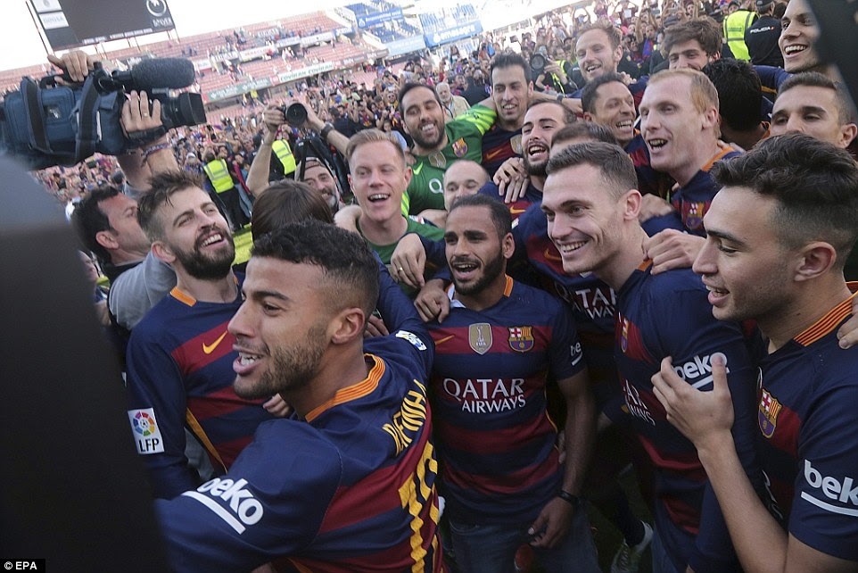 Barcelona players celebrate after the final whistle as hundreds of fans invaded the pitch following their latest league title win