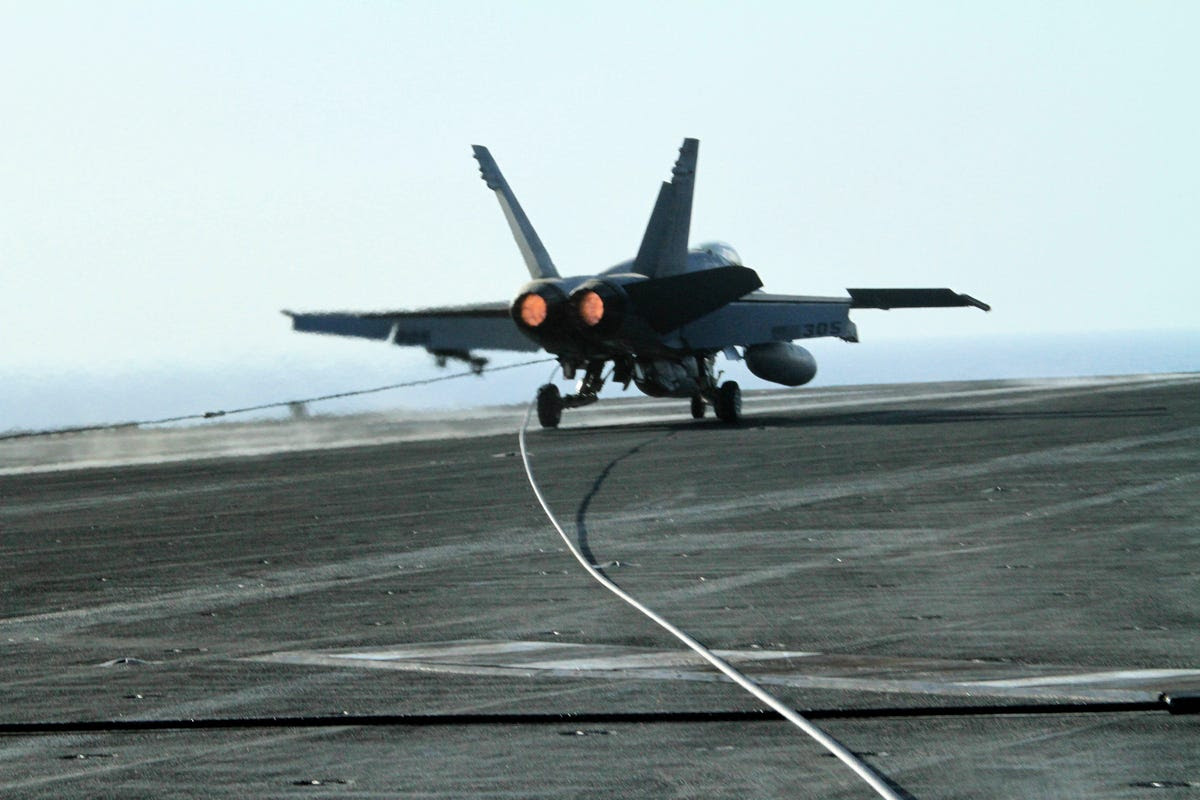 The aircraft rips the steel cable from its coil before reversing its afterburners and coming to a halt.
