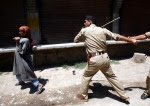 P19-6-07-An Indian police officer tries to hit a Kashmiri wo