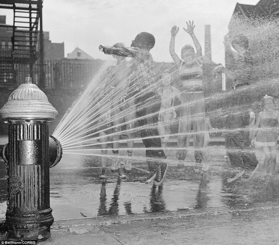 Fire hydrant fun: Children welcomed sweltering weather in 1954 because it gave them a chance to frolic under the spray of fire hydrants; pictured, near New York City's Columbus Circle