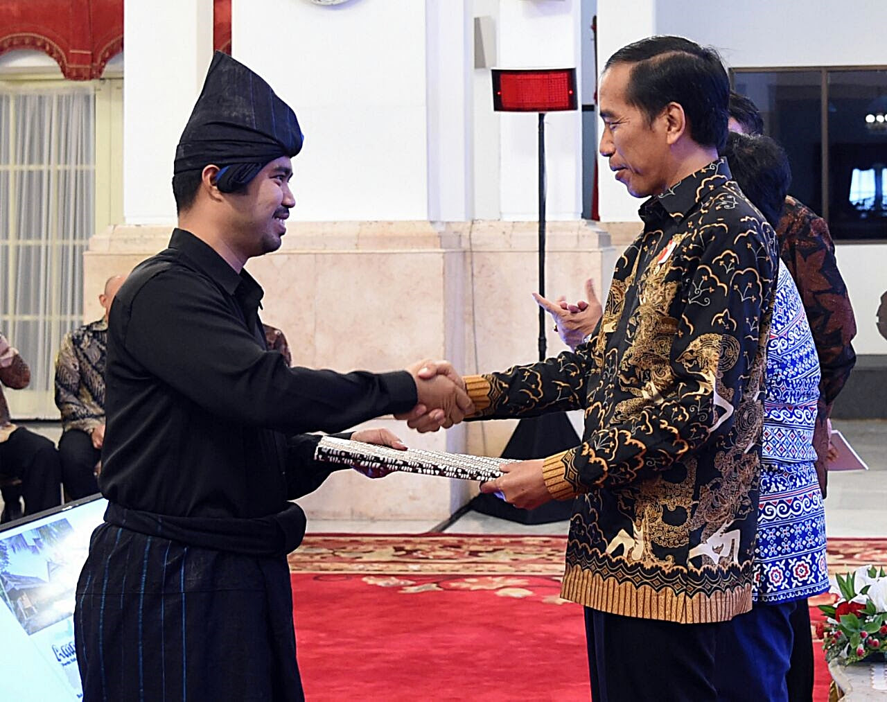 Andi Buyung Saputra, Kajang leader, left, receiving the title from President Joko Widodo.