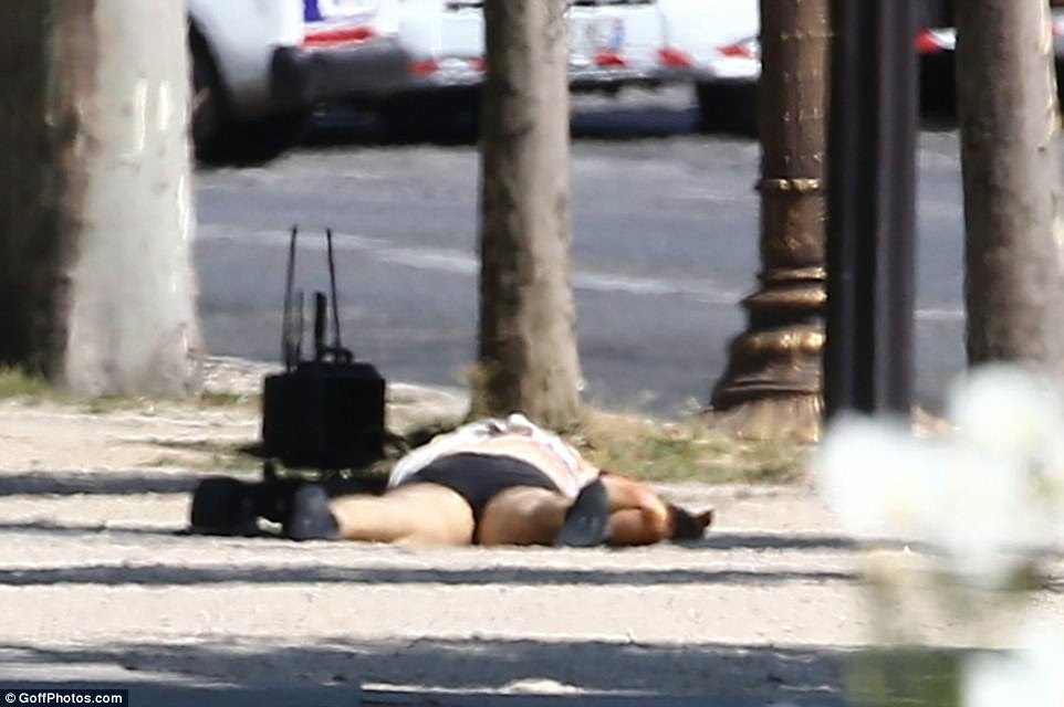 The driver sprawled on the pavement with a bomb disposal robot nearby after a police officer ripped his clothes from him