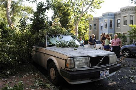 People survey storm damage in the Capitol Hill neighborhood in Washington, June 30, 2012. Wind gusts clocked at speeds of up to 79 mph were reported in and around the U.S. capital, knocking out power to hundreds of thousands of homes in the Washington area. REUTERS-Jonathan Ernst