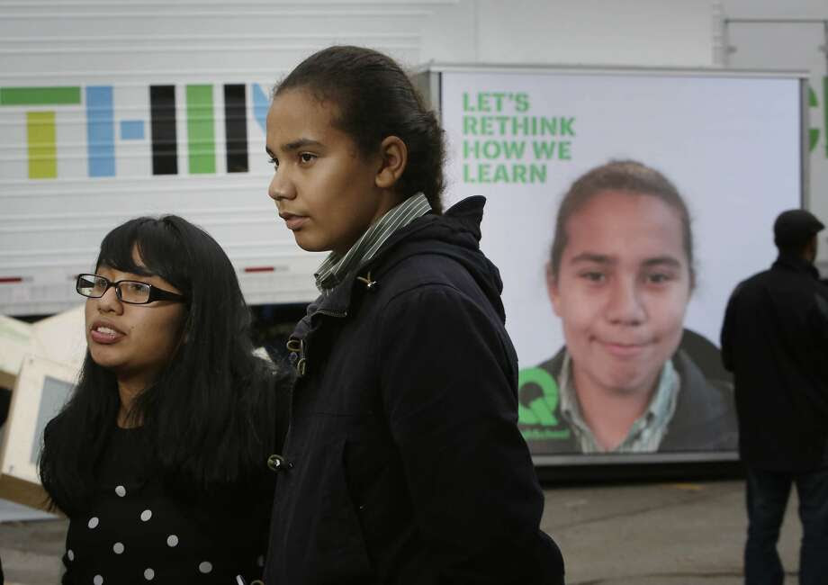 Maya Martin (l to r), 16, junior West High School, Aaron Jackson, 15, sophomore West High School stand together as they are interviewed for a promotional video at the XQ roadshow while Jackson's image is displayed on the XQ We Think booth behind her on Wednesday, December 9,  2015 in Oakland, Calif. Photo: Lea Suzuki, The Chronicle