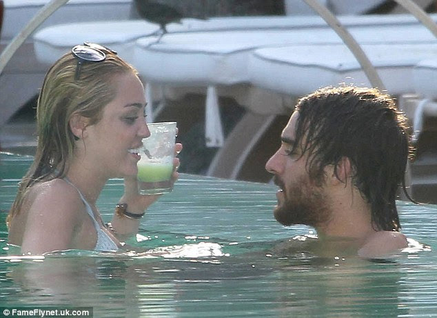 Look away now Liam! Newly engaged Miley Cyrus was pictured looking very close to her male friend Cheyne Thomas as they frolicked in a pool in Miami yesterday