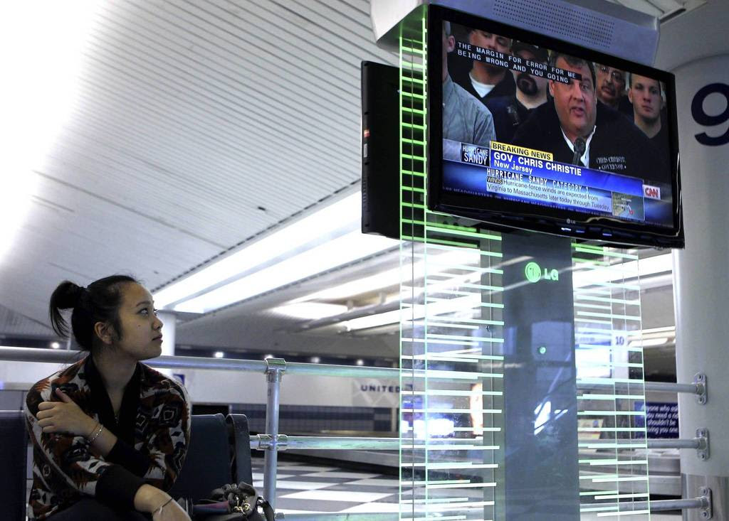 Seattle resident Navy Duong watches hurricane coverage on the East Coast on the baggage claim level of O'Hare International Airport. Duong was headed to New York on Monday to see family, but her flight has been delayed until Wednesday, stranding her in Chicago.