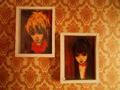 Two vintage doll's house big eye' pictures on a lounge wall.