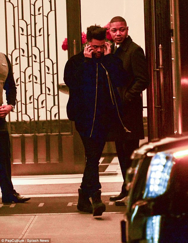 Clamped to his ear: The Weeknd talked on his cell phone as he left Bella's place