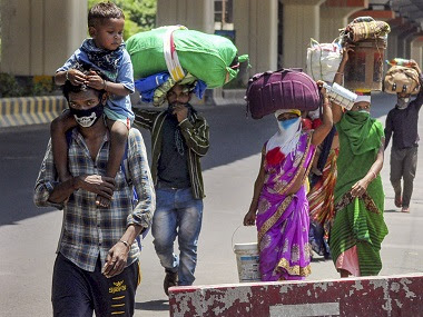 Migrant workers from Balaghat (MP) carry their belongings as they walk towards their native places. PTI