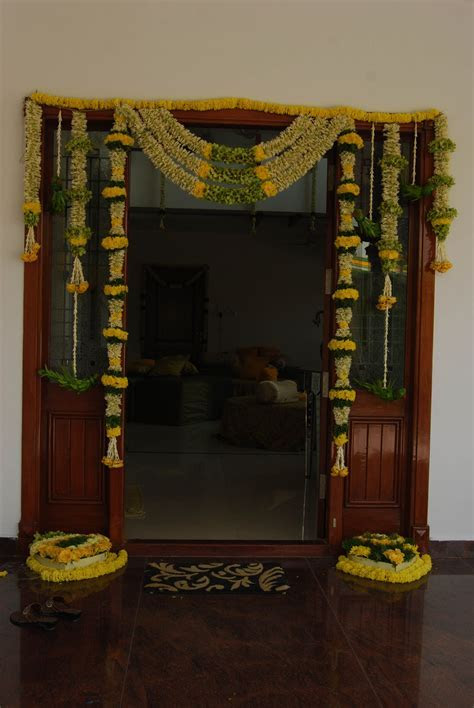 Door framed by flowers and green leaves   Pasupu Kottadam